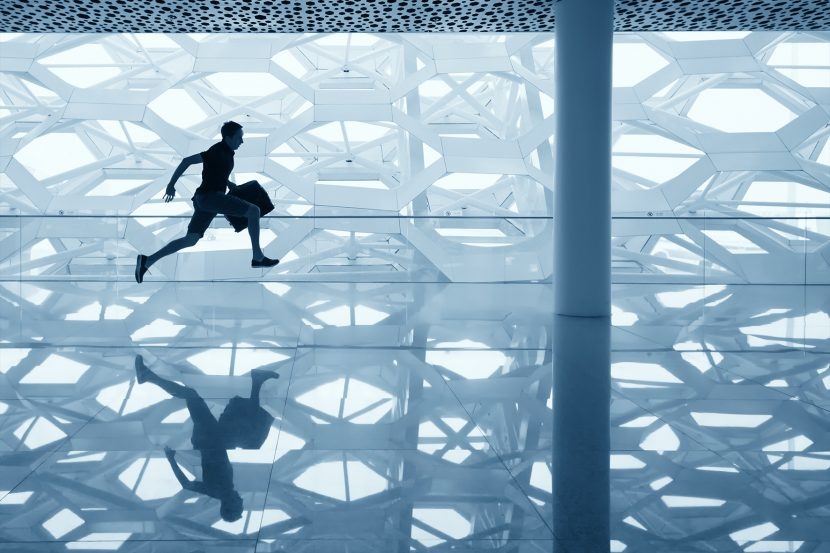 Men's health article on reducing stress feature image of man running with briefcase in architectural space