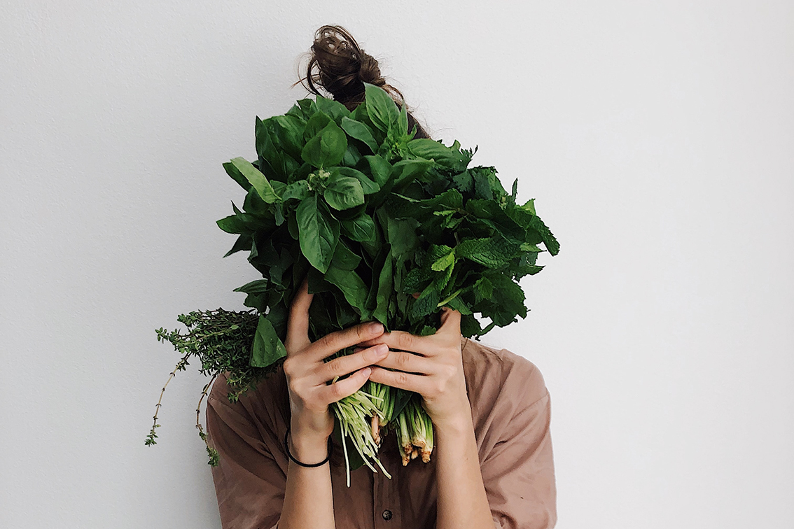 Woman holding bunch of herbs in nutrition article by dietitian Caylin Goodchild.
