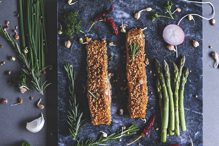 Fatty fish Salmon on slate chopping board with asparagus, garlic and shallots by photographer Natalie Field